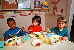 Three preschool children eat a meal. Link to photo information