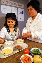 Nursing assistant samples a low-carotene lunch served by dietitian Doris DeLeon.