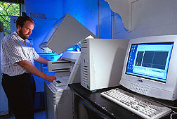 A high-capacity DNA sequencer being loaded by geneticist Curt Van Tassell.