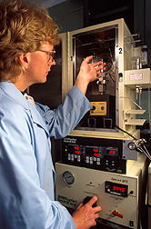Chemist adjusts the pressure-control gauge on a device while a biocatalysis reaction occurs inside. Click here for full photo caption.
