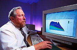 Researcher examines output from a software program used for predicting the performance of spillways and designing new structures. Click here for full photo caption.