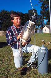 Daniel Kline inspects mosquitoes caught in a collection device: Link to photo information
