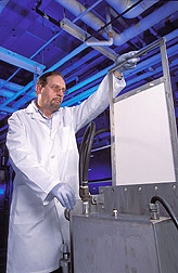 Chemical engineer inspects a sample of cotton fabric: Click here for full photo caption.