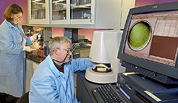 Microbiologist and technician use computer-assisted laboratory methods to record growth of Listeria monocytogenes bacteria on meat products: Click here for full photo caption.