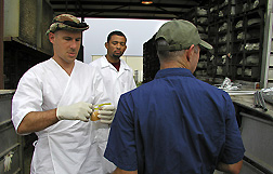 Microbiologist, student, and technician collect a sponge sample from the floor of a transport coop: Click here for full photo caption.