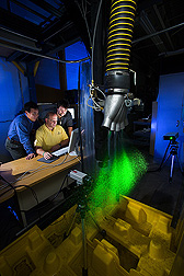 Agricultural engineers and technician use a pulsed laser and a high-speed video camera to analyze the size and speed of water droplets: Click here for full photo caption.