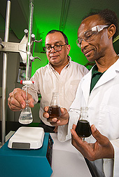 ARS technician (right) shows fabrication superintendent of Alma Sugarcane Factory, Lakeland, Louisiana, the dextranase activity titration method for use at the factory: Click here for full photo caption.