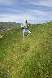 Agriculturalist studies a roadside bank covered in ripening cheatgrass in Utah: Click here for full photo caption.