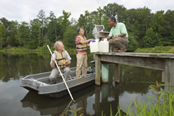 Microbiologist (left) and technician (center), with the help of agricultural engineer (on the dock), unload the water samples for microbial analysis: Click here for full photo caption.