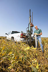 Technician Kent Heikens prepares a large core sampler to take a core sample of the wood chip bioreactor beneath a soybean field for lab analysis of denitrification rates and bacterial populations: Click here for photo caption.