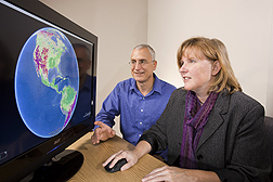 Photo: ARS scientists Martha Anderson and Bill Kustas examine a computer screen projection from a drought modeling system. Link to photo information
