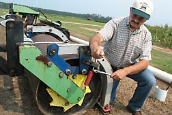 Agricultural engineer Ted Kornecki adjusts the crimping force of his patented smooth roller with oscillating crimping bar: Click here for photo caption.