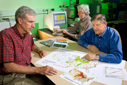 Soil scientist Ron Follett (right) examines a map of ARS soil carbon research sites across the United States while physical science technician Ed Buenger conducts mass spectrophotometer analysis of soil samples for carbon and nitrogen: Click here for photo caption.