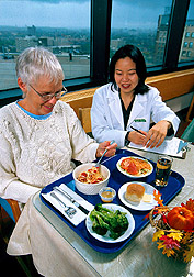 Dietitian instructs a study volunteer on the foods to be eaten as part of the metabolic study. Click here for full photo caption.