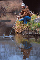 Technician Jeff Nichols collects a water sample from the Walnut Creek watershed. Click here for full photo caption.