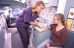 In mobile  lab, technician collects blood sample from student participating in nutrition study. Link to photo information