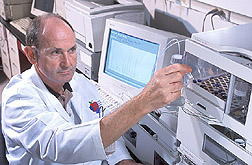 Neuroendocrinologist inserts a sample into a mass-spectroscopy unit: Click here for full photo caption.