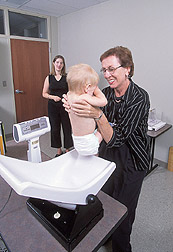 Photo: Nutritionist Pat Wiggins weighs a 1-year-old boy while his mother watches. Link to photo information
