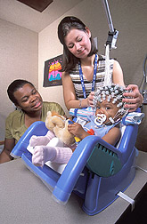 Research assistant places a neural net on an 8-month-old study participant: Click here for full photo caption.
