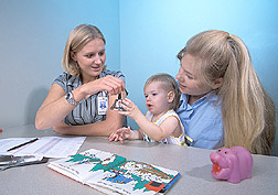Psychological examiner (left) uses the Bayley Scales of Infant Development Assessment: Click here for full photo caption.