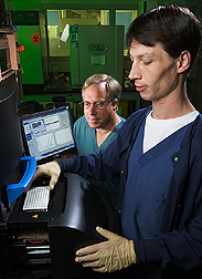 Microbiologist and technician load samples into a fluorescent real-time thermocycler: Click here for full photo caption.