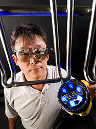 Scientist Moon Kim wearing a tiny head-mounted display monitor resembling a pair of safety glasses. Link to photo information