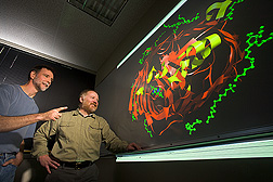 Molecular biologist (left) and computational biologist examine a molecular model of a protein involved in iron uptake by bacteria: Click here for full photo caption.