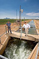 At the Central Arizona Irrigation and Drainage District, hydraulic engineer (left) and electrical engineer assess the automatic control of one of the many hydraulic gates operated by ARS-developed software while student (background) checks the communications: Click here for full photo caption.