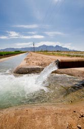 Photo: Water flowing from a pipe into an irrigation canal. Link to photo information