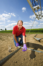 Soil scientist applies pelletized gypsum and polyacrylamide (PAM) to a soil surface to control erosion prior to a rainfall-simulation test: Click here for full photo caption.