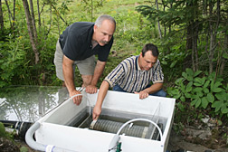 ARS agricultural engineer (right) and soil scientist of Spectrum Research, Inc., inspect a filter cartridge system being evaluated at a golf course tile drainage site: Click here for full photo caption.