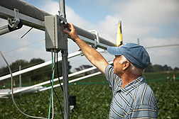 Research leader Don Ort inspects a switch for a device that allows him to adjust a variable in the soybean field: Click here for photo caption.