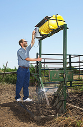 Entomologist David Taylor adjusts the settings on a sprayer used to automatically treat cattle with a stable fly repellent: Click here for photo caption.
