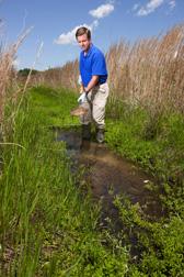 Ecologista Matt Moore examina el suelo y la vegetación en una zanja de desagüe. Enlace a la información en inglés sobre la foto