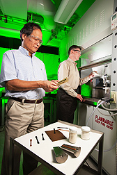 Plant physiologist Arland Hotchkiss (right) adds sugar beet pulp and polylactic acid to an extruder to make the bioplastic strips that chemist LinShu Liu is inspecting: Click here for photo caption.