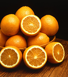 Photo: A bowl that is full of whole and cut oranges. Link to photo information