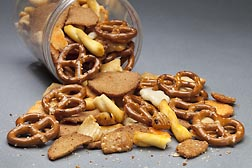 A container of pretzels, crackers and sesame sticks. Link to photo information