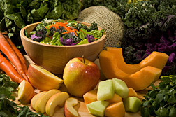 Carrots, apples, melons and salad greens surrounding a bowl of salad.  Link to photo information