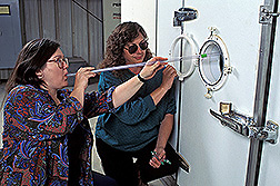 Entomologist Judy Johnson (left) and technician Karen Valero use tubes to insert moths into storage rooms. Click here for full photo caption.