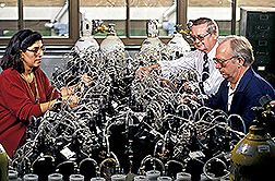 Two chemists and a technician inspect the experimental setup for news ink biodegradation tests. Click here for full photo caption.
