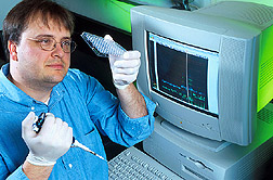 Geneticist prepares to load PCR samples onto an automated DNA sequencer. Link to photo information.