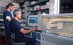 Two microbiologists performing DNA sequencing: Click here for full photo caption.