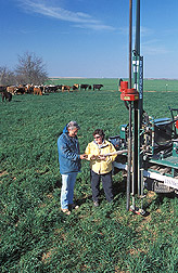 Technician and meteorologist perform a soil core extraction: Click here for full photo caption.