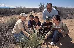Nature Park director and station superintendent work with children on a field trip: Click here for full photo caption.