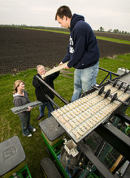 Geneticist, technician, and research assistant load soybeans on a plot planter: Click here for full photo caption.