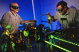 Two microbiologists evaluate a new laser: Click here for full photo caption.