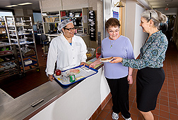 Nutrition technician (left) and nutritional biochemist (right) discuss a study diet with a participant: Click here for full photo caption.