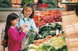 Parents who want their kids to eat more fruits and vegetables may involve the youngsters in helping to select items from the supermarket produce section: Click here for photo caption.