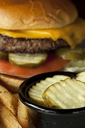 A cheeseburger on a bun with container of pickle slices. Link to photo information