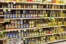 Pickled vegetables and relishes fill several grocery store shelves.